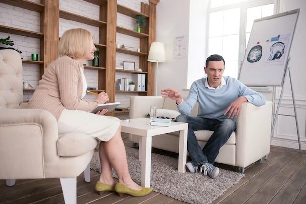 Wait a minute. disturbed musing man posing during therapy while explaining his problem to psychologist