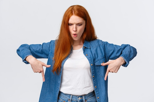 Wait a minute what is that. frustrated and angry tensed redhead girlfriend asking wtf going on, dont understand, looking perplexed and mad down, pointing bottom copy space, stand white