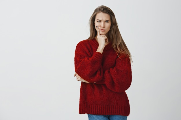Wait a sec. perplexed moody charming sexy girlfriend in red loose sweater pouting frowning focused and thoughtful touching face, squinting with disbelief and doubt having suspicious feeling