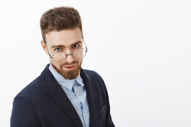 Wait-up shot of charming successful and intelligent european male with beard and blue eyes looking from under glasses with sexy expression standing in elegant suit posing against white wall