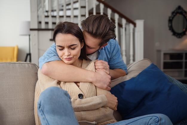 Подождите. взволнованный молодой человек утешает свою подругу, нежно касаясь ее руки. женщина держит мобильный телефон и смотрит на парня с обидой