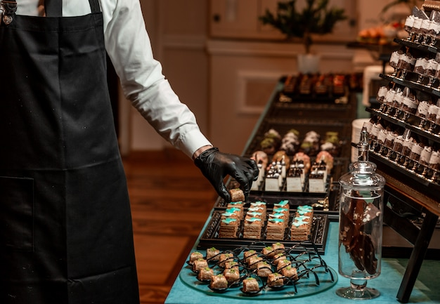 Waiter adjusts a banquet table with sweets