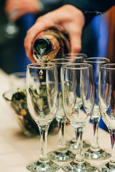 Waiter bartender pours champagne from a bottle into glasses