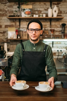 Waiter in black apron holds two cups of coffee in his hands.