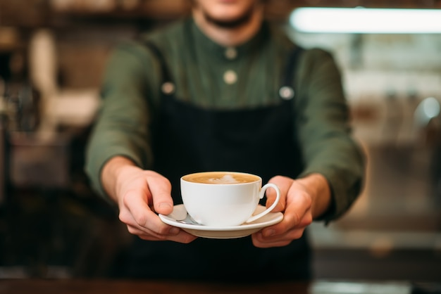 Waiter in black apron stretches a cup of coffee with cream in hands.