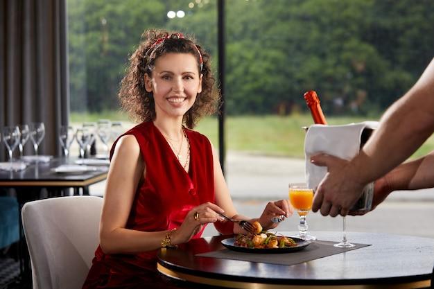 レストランで若い女性にシャンパンと氷のバケツを持ってウェイター