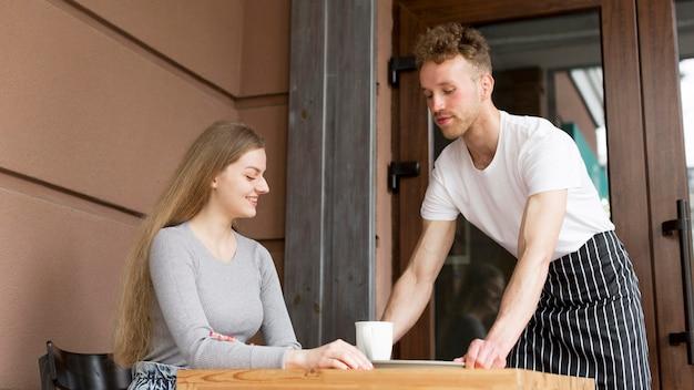 Официант приносит кофе женщине