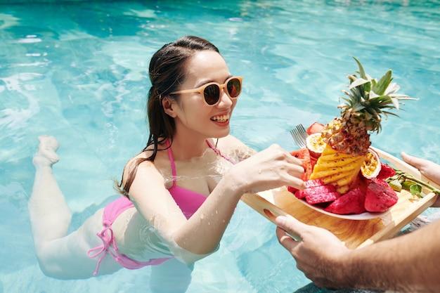 スイミングプールに果物をもたらすウェイター
