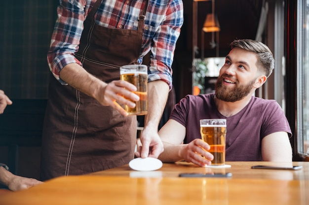 Waiter in brown apron bringing beer for two happy bearded men in bar