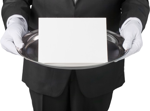 Waiter or butler wearing a tuxedo holding a note card on a silver tray in front of his torso.