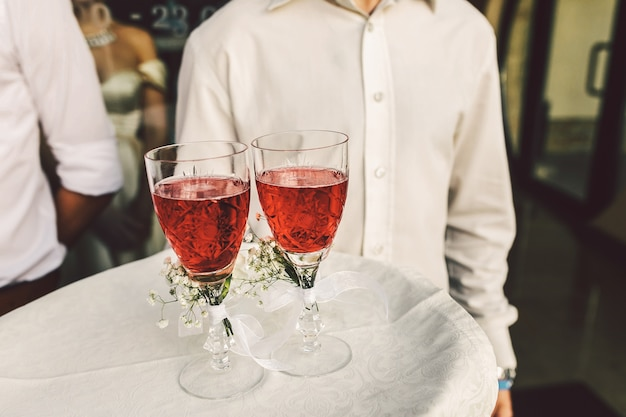 Waiter carries glasses with red drink and decorated with little daisies