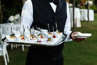 ウェイターはおいしい軽食とプレートを運ぶ
