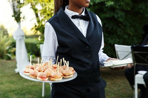 Il cameriere porta la piastra con gustosi snack