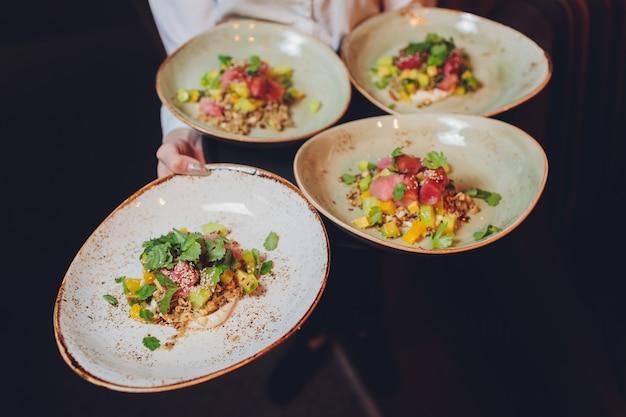 Официант несет тарелку с рыбой и салатом на свадьбу.