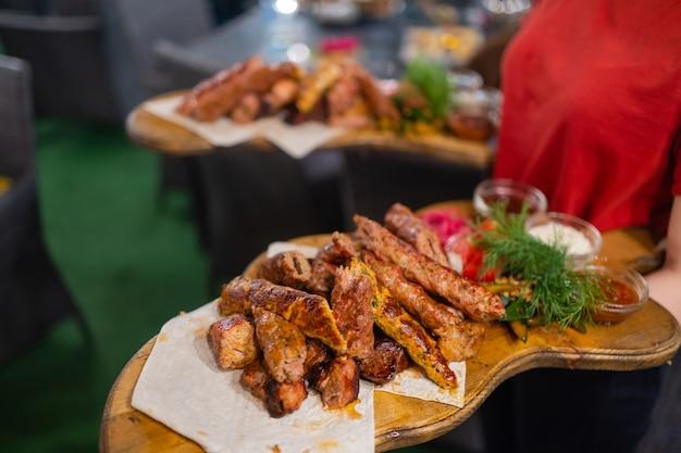 いくつかのお祝いイベント、パーティー、結婚披露宴、またはケータリングイベントで肉料理と2つのプレートを運ぶウェイター。