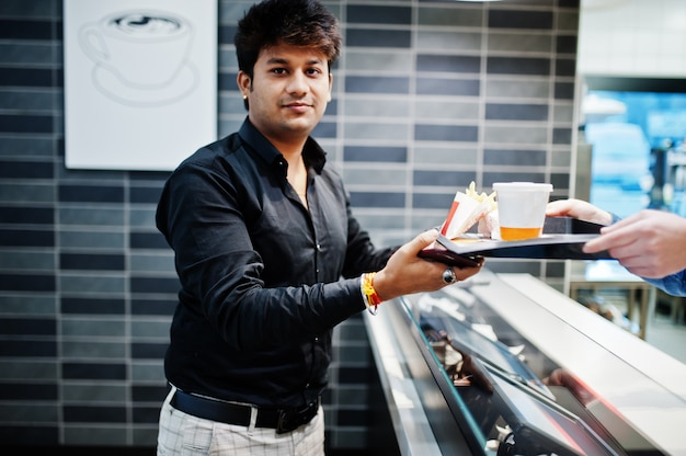 Waiter cashier gives order on food tray to stylish indian man.