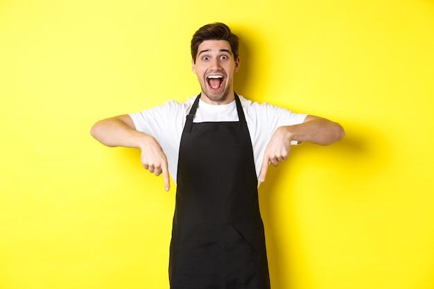 ウェイター、黒いエプロンで指を下に向け、驚いたように見え、黄色の背景の上に立っているコーヒーショップのバリスタ。