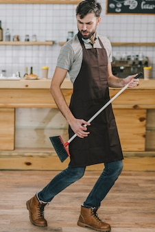Waiter dancing with broom