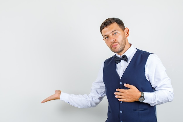 Waiter gesturing welcome in shirt, vest and looking careful. front view.
