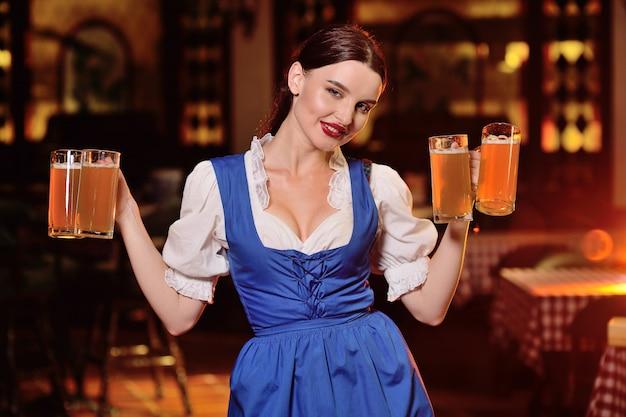 Девушка-официантка с большой грудью в баварской одежде держит много пивных кружек в баре во время празднования октоберфеста