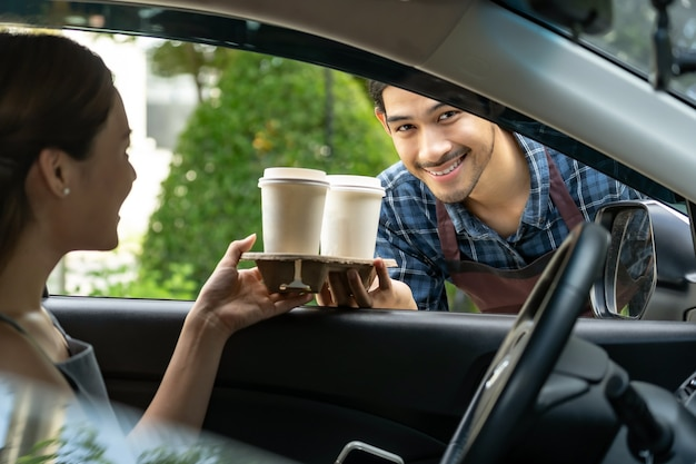 Waiter giving hot coffee cup with disposable tray through car window to customer