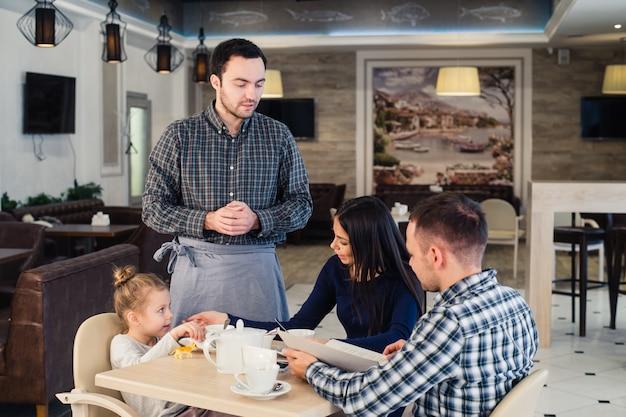 ウェイターがカフェで幸せな家族にメニューを与える