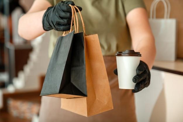 도시 covid 19 잠금, 코로나바이러스 폐쇄 동안 웨이터가 테이크아웃 식사를 제공합니다. 알아볼 수 없는 여성 웨이터, 장갑을 낀 여성 손은 테이크아웃 주문으로 일합니다. 음식 커피 배달.