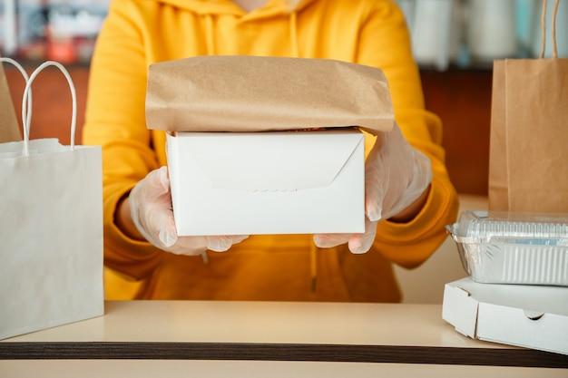 테이크 아웃 식사를하는 웨이터가 테이크 아웃 주문을하는 동안 테이크 아웃 식사를하는 동안 도시 covid 봉쇄 코로나 바이러스 종료 베이킹 테이크 아웃 피자 커피 음식 배달 장갑을 입은 여성