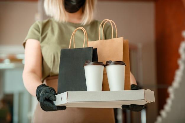 도시 covid 봉쇄 코로나 바이러스 종료 인식 할 수없는 여성 웨이터가 보호용 의료 마스크와 장갑을 착용하고 테이크 아웃 주문을하는 동안 테이크 아웃 식사를하는 웨이터 음식 피자 커피 배달