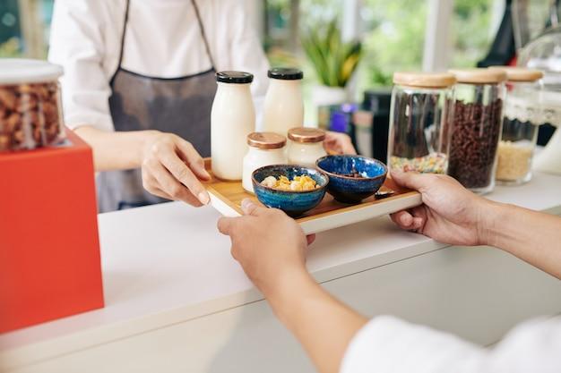 ウェイターがお客様に朝食付きのトレイを与える
