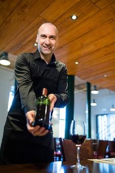 赤ワインのボトルを保持しているウェイター