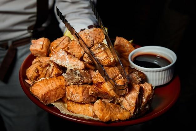 Официант держит большое блюдо с кусочками лосося на гриле
