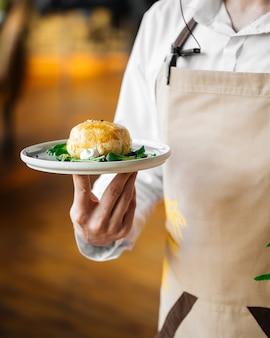 퍼프 페이스 트리에 구운 카망베르 치즈와 함께 접시를 들고 웨이터