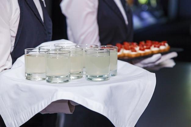 Официант с подносом предлагает гостям на мероприятии стакан лимонада.