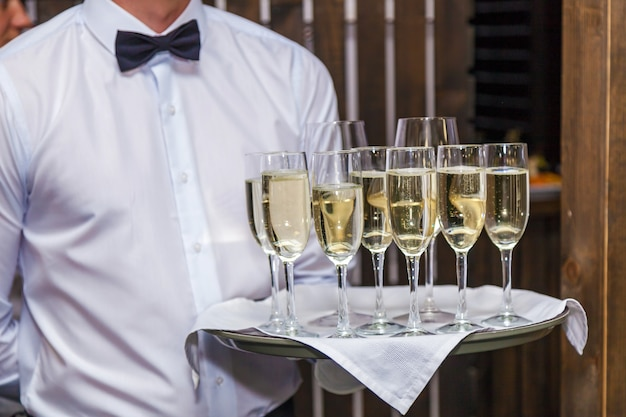 Официант с подносом предлагает гостям мероприятия