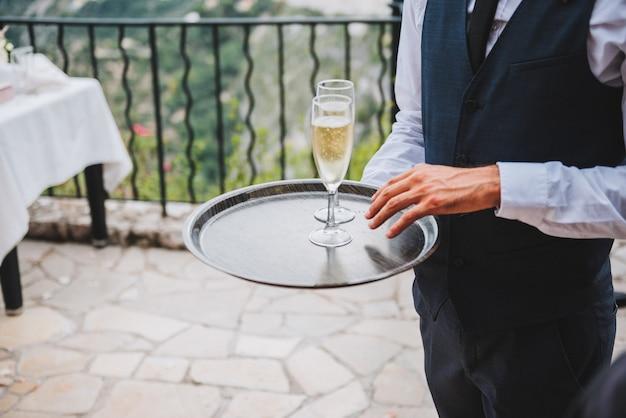 パーティーや社交イベントでシャンパン2杯またはスパークリングワインのトレイを保持しているウェイター
