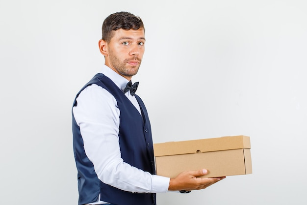 Waiter holding cardboard box in shirt, vest and looking cheerful.