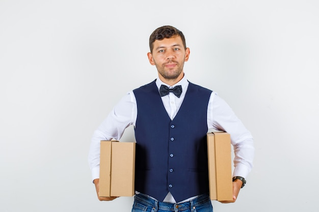 Waiter holding cardboard boxes and smiling in shirt, vest, jeans , front view.