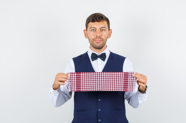 Waiter holding checked towel in shirt, vest and looking focused. front view.
