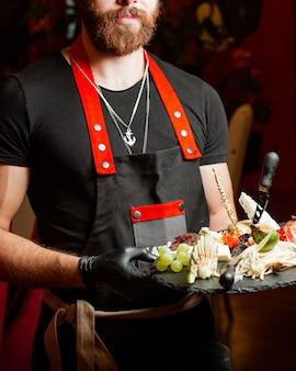 Официант держит сырную тарелку с орехами и медом