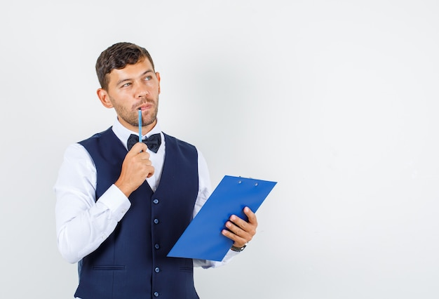 Waiter holding clipboard and pencil in shirt, vest and looking pensive , front view.