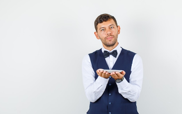 Waiter holding empty plate in hands in shirt, vest front view.