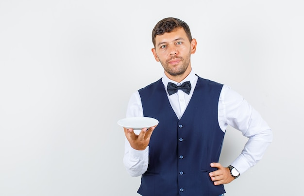 Waiter holding empty plate with hand on waist in shirt, vest and looking gentle. front view.