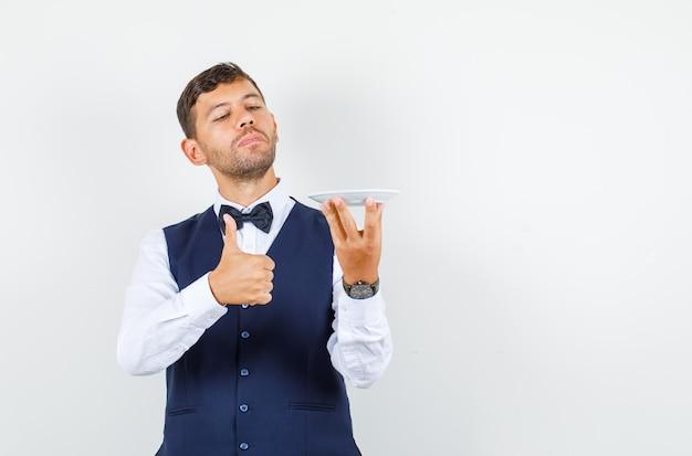 シャツに親指を立てて空のプレートを保持しているウェイター、ベストの正面図。