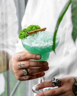 Waiter holding a glass of green cocktail garnished with broccoli and cinnamon stick