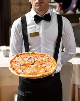 Cameriere che tiene la pizza ai peperoni con i funghi