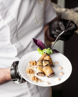 Waiter holding a plate of fried aubergine wraps with walnuts