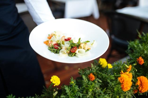 Официант держит тарелку салата из креветок для гурманов