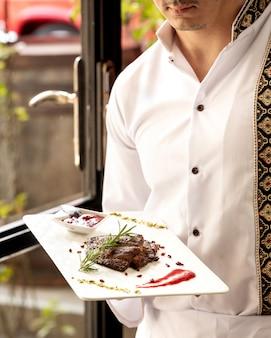 Il cameriere che tiene un piatto di pezzi di bistecca è servito con salsa acida