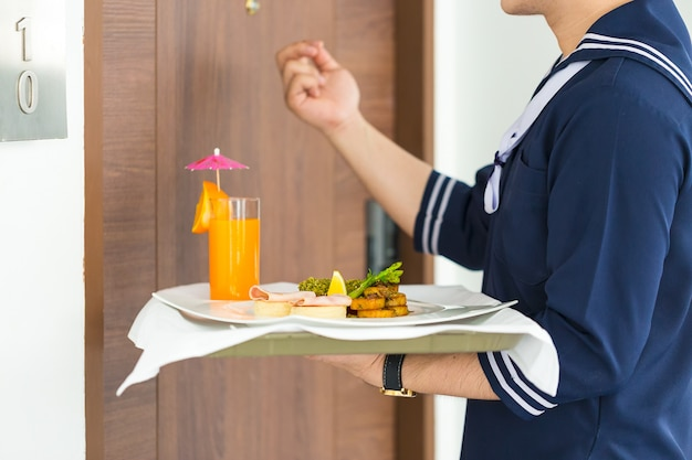 Waiter holding plate with breakfast and knocking door in front of a hotel room.